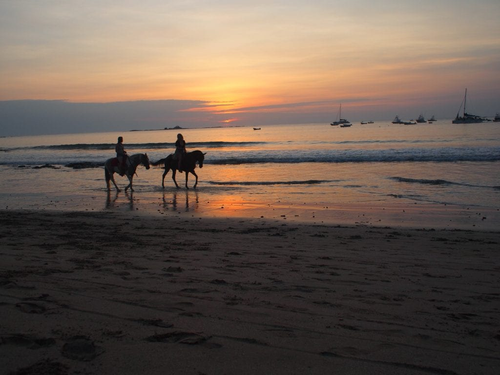 Taking in the sunset with horseriders going past on a Tamarindo beach, Costa Rica